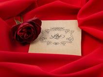 Cartellino rosso sul panno rosso con una rosa Fotografia Stock