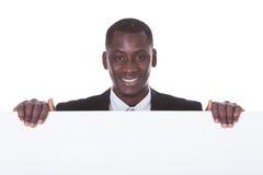 Cartello africano della tenuta dell'uomo d'affari fotografie stock