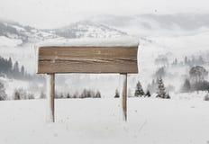 Cartello di legno con meno neve e montagne Fotografia Stock Libera da Diritti
