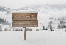 Cartello di legno con neve e le montagne Fotografia Stock