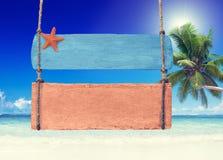 Cartello di legno variopinto che appende su una spiaggia tropicale immagini stock libere da diritti