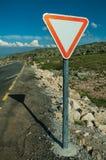 Cartello di traffico del RENDIMENTO sul bordo della strada e sul paesaggio roccioso immagine stock libera da diritti