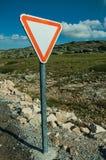 Cartello di traffico del RENDIMENTO sul bordo della strada e sul paesaggio roccioso fotografia stock