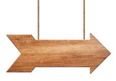 Cartello o insegna di legno di forma della freccia fatta di legno naturale che appende sulle corde illustrazione di stock
