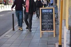 Cartellone pubblicitario della lavagna della via della caffetteria con la gente che cammina vicino Immagine Stock