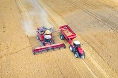 Cartels et tracteurs travaillant au champ de blé Photographie stock libre de droits