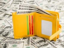 Cartera amarilla que descansa sobre mucho cientos dólares Foto de archivo libre de regalías