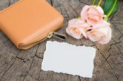 Cartera con las flores y el documento sobre fondo de madera Fotografía de archivo libre de regalías