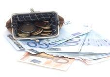 Cartera con las monedas y los billetes de banco euro en el fondo blanco Foto de archivo