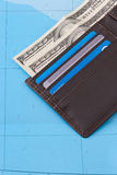 Cartera con las tarjetas del efectivo y de crédito de los dólares en fondo del mapa Imágenes de archivo libres de regalías