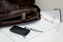 Cartera con los documentos, la pluma y el teléfono móvil Fotografía de archivo libre de regalías