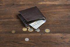 Cartera de cuero con los dólares en un fondo de madera