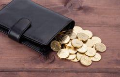 Cartera de cuero negra con las monedas de oro en el fondo de madera Imagen de archivo libre de regalías