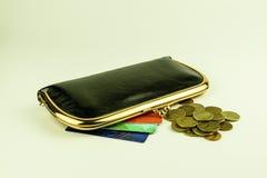 Cartera de cuero negra del ` s de las mujeres, tarjetas coloridas del descuento y monedas Foto de archivo libre de regalías