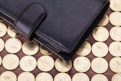 Cartera de cuero negra en moneda de oro Fotografía de archivo