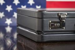 Cartera de cuero que descansa sobre la tabla con la bandera americana detrás Fotografía de archivo libre de regalías