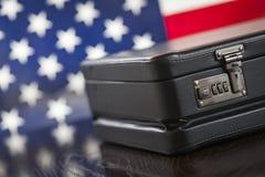 Cartera de cuero que descansa sobre la tabla con la bandera americana detrás Imagen de archivo