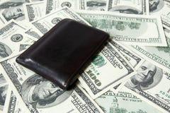 Cartera de cuero y cientos billetes de dólar Imagen de archivo