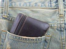 Cartera en un bolsillo trasero de vaqueros del dril de algodón como fondo Imagen de archivo libre de regalías