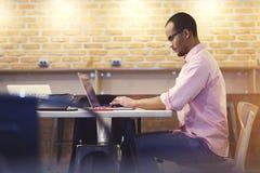Cartera joven de la fijación del profesor y del estudiante y cv en sitio web del empleo vía el ordenador portátil y el wifi Imagen de archivo libre de regalías