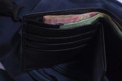 Cartera negra con el baht del dinero Imagenes de archivo