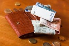 Cartera y un poco de dinero en una tabla del woden Foto de archivo