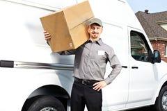 Cartero con el paquete cerca del camión de reparto fotografía de archivo