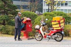 Cartero con la motocicleta y el correo Imagen de archivo libre de regalías