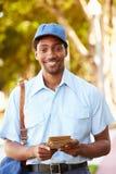 Cartero Walking Along Street que entrega letras Imagenes de archivo