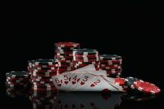 Cartes avec une victoire et des jetons de poker dans l'obscurité sur un fond noir Photos stock