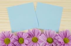 Cartes bleues vierges et fleurs roses sur le fond en bois Photo libre de droits