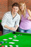 Cartes de jeu caucasiennes de couples sur un billard Photo stock