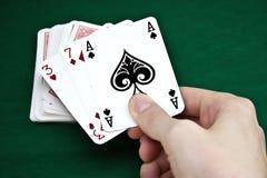 Cartes de jeu dans une main Photographie stock libre de droits