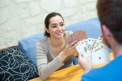 Cartes de jeu heureuses de couples ? la maison images stock