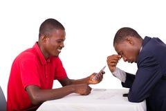 Cartes de jeu de jeunes hommes à la table de jeu photographie stock