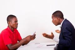 Cartes de jeu de jeunes hommes à la table de jeu image libre de droits