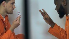 Cartes de jeu multiraciales délicates de prisonniers in camera, divertissements de risque banque de vidéos