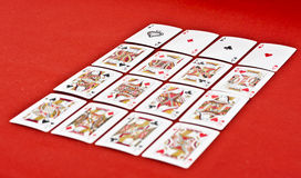 Cartes de jeu sur le tissu rouge Photos libres de droits
