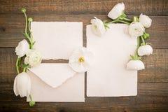 Cartes de papier de vintage, enveloppe et fleurs blanches sur le fond en bois Configuration plate, vue supérieure Image stock
