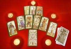 Cartes de Tarot avec des bougies sur le textile rouge Photographie stock libre de droits