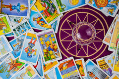 Cartes de Tarot avec une bille magique sur une table pourprée. Image libre de droits