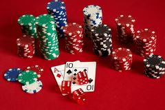 Cartes de tisonnier et puces de jeu sur le fond rouge Photos stock