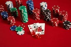 Cartes de tisonnier et puces de jeu sur le fond rouge Photos libres de droits
