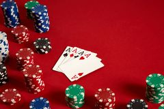 Cartes de tisonnier et puces de jeu sur le fond rouge Photographie stock