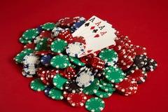 Cartes de tisonnier et puces de jeu sur le fond rouge Image libre de droits