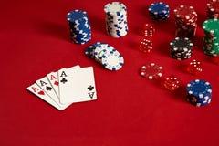Cartes de tisonnier et puces de jeu sur le fond rouge Image stock