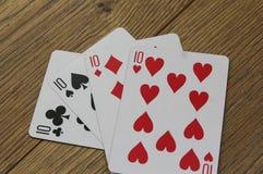 Cartes de tisonnier sur un backround en bois, l'ensemble de dizaines de clubs, les diamants, les pelles, et les coeurs Images libres de droits