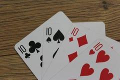 Cartes de tisonnier sur un backround en bois, l'ensemble de dizaines de clubs, les diamants, les pelles, et les coeurs Photo libre de droits