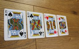 Cartes de tisonnier sur un backround en bois, l'ensemble de rois de trèfle, les diamants, les pelles, et les coeurs Image libre de droits