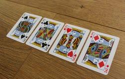 Cartes de tisonnier sur un backround en bois, l'ensemble de rois de trèfle, les diamants, les pelles, et les coeurs Photographie stock